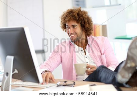 Young smiling man in office with feet on desk