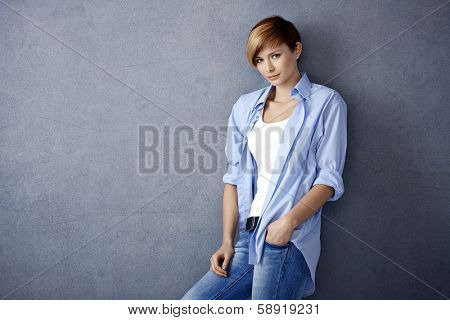 Casual young woman leaning to wall, hand in pocket