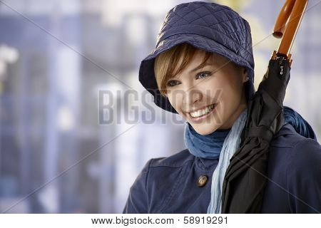 Portrait of attractive young woman with umbrella, smiling.