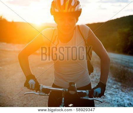 mountain biker on road against sunset