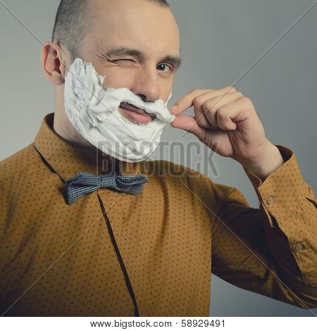 Hipster. Funny portrait of trendy man making moustache and beard of shaving foam and gives wink, toned.