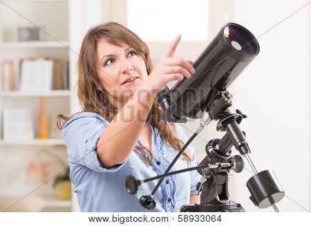Beautiful woman looking skyward and pointing something in the sky standing near a window with astronomical telescope