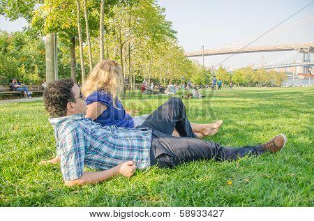 Inter-ethnic couple resting in Brooklyn Bridge Park, New York
