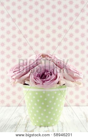 Flowers In A Green Polkadot Vase On Vintage Wooden Background