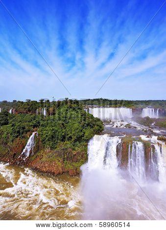 The grand Iguazu Falls on the Brazilian side. Multi-tiered cascades of water roar of lush jungle. Over boiling water swirls fine mist