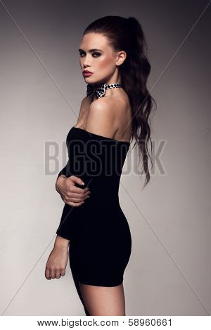 Beautiful sultry young woman in a glamorous elegant off the shoulder black cocktail dress standing sideways giving the camera a seductive look