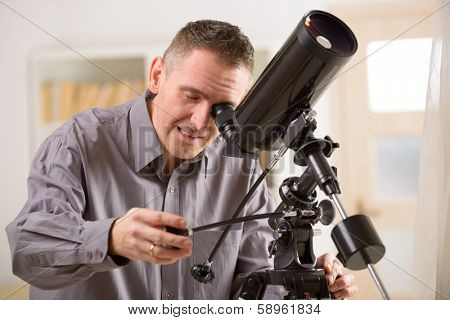 Man looking skyward through astronomical telescope standing near a window