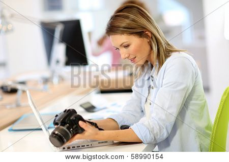 Woman reporter in office looking at photo camera poster