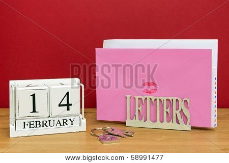 A Valentines day card sealed with a red lipstick kiss in a letterack, with a date block showing 14th February.