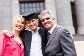 portrait of happy female university graduate and parents at ceremony poster