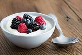 Bowl of fresh mixed berries and yogurt with farm fresh strawberries blackberries and blueberries served on a wooden table poster