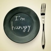 picture of a fork and a plate painted as a blackboard with the text I a??m hungry written in it on a beige background with a retro effect poster
