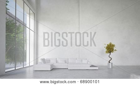 Double volume spacious living room interior with huge panoramic windows overlooking a garden and a corner unit white lounge suite against a bare white wall