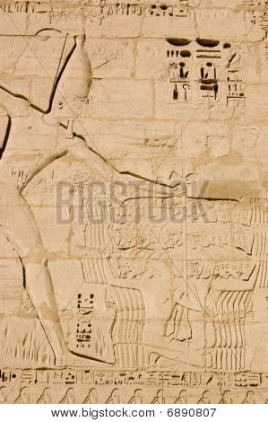 A huge hieroglyphic carving of the ancient egyptian Pharoah Ramses II holding a group of his defeated enemies by ropes around their necks with a view to killing them with a weapon in his right hand.  This large carving is on an outer Pylon wall of the Tem poster