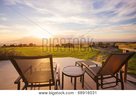 Lounge chairs on deck at sunset