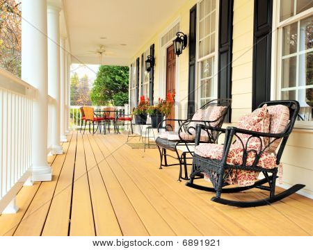 Low angle view of a large front porch with furniture and potted plants. Vertical format. poster