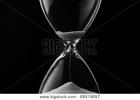 Sand Trickling Through The Bulbs Of An Hourglass