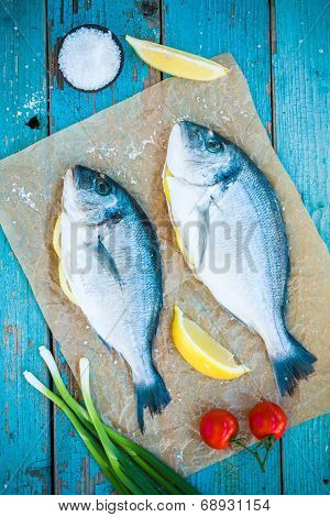 Two Raw Dorado Fishes  Fishes With Lemon, Green Onions And Cherry Tomatoes