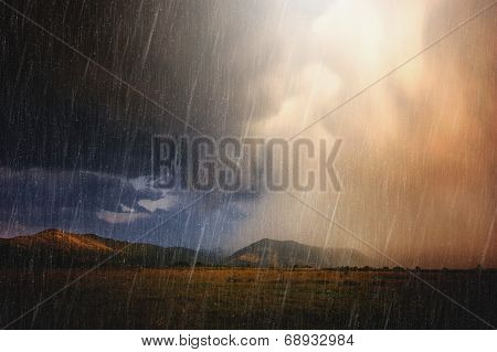 Heavy storm with clouds and lightning over mountain and meadow