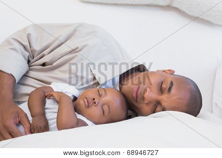 Happy young father with baby son on couch at home in the living room