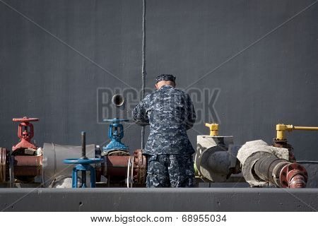 STATEN ISLAND, NY - MAY 25, 2014: A member of the U.S. Navy turns one of the large valves along side of the guided-missile destroyer USS Cole (DDG 067) moored at Sullivans Piers for Fleet Week NY.