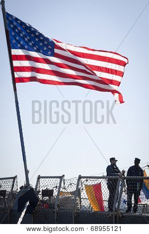 STATEN ISLAND, NY - MAY 25, 2014: The American flag flies from the stern of the guided-missile destroyer USS McFaul (DDG 074) docked at Sullivans Piers during Fleet Week NY on May 25, 2014.