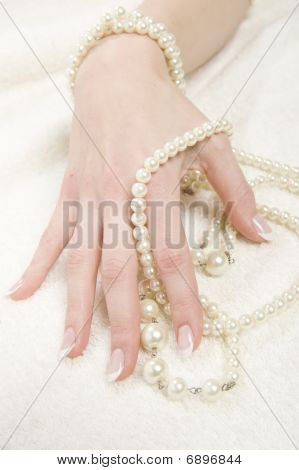 beautiful hands with healthy skin and perfect french manicure and pearl nechlace