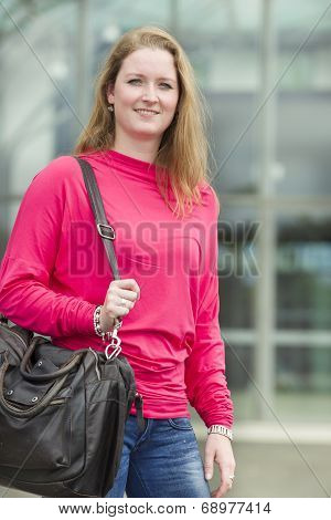 Young Student Smiling With Her Bag In Her Hands