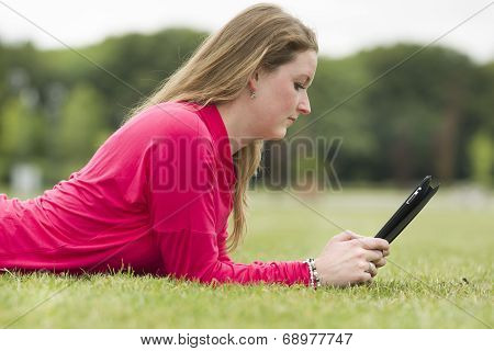 Student Lies In The Grass And Looks At Her Ipad
