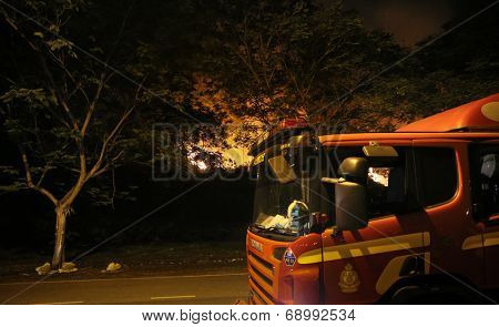 PUCHONG, MALAYSIA - JULY 26, 2014: Fire-fighters arrive to fight the blaze in a forest fire at the foot hills of the Air Hitam Forest Reserve. The recent drought makes the forest susceptible to fires.