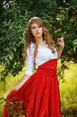 Romantic portrait of the woman in red skirt standing under the tree poster
