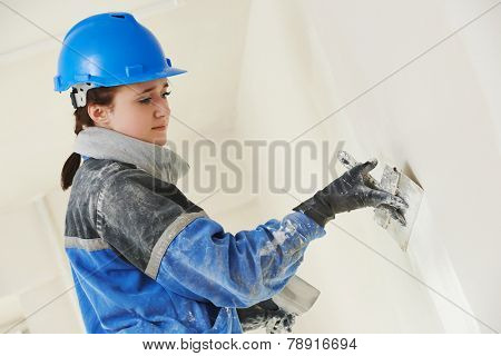 female plasterer painter at indoor wall renovation decoration stopping with spatula and plaster poster