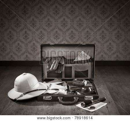 Colonial style explorer packing with open leather briefcase pith hat leather gloves maps and brass telescope. poster