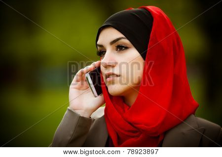 Beautiful muslim woman wearing hijab outdoor portrait. Muslim woman talking on the phone and using t