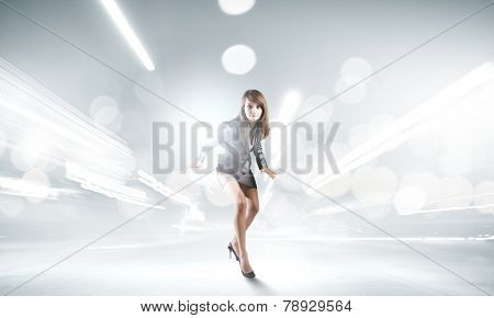 Young businesswoman in suit running against bokeh background