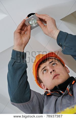 electrician worker in uniform installing or replacing spot light lamp into ceiling poster