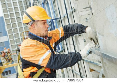 worker builder making construction for ventilation facade on a building with screwdriver drill poster