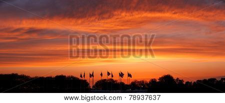 U.S. Flags standing under a glowing cloudy sky lit by the setting sun. Horizontal panoramic of American banners on Flag Plaza in Liberty State Park, NJ. Red, orange and golden clouds at sunset. poster
