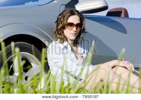 Woman Is Sitting Near A Car