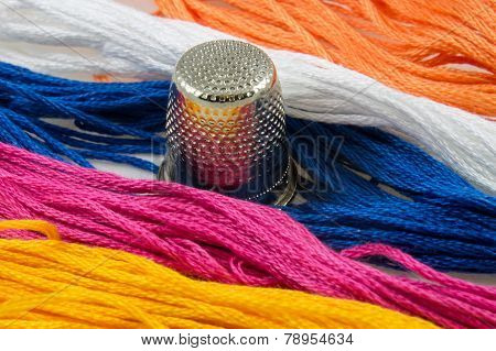 Strands Of Colored Cotton And A Thimble