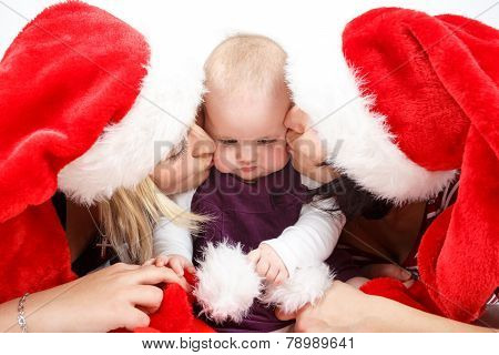 Two Womans With Santa Hat Kissing Baby