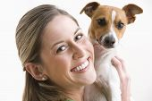 An attractive young woman is looking over her shoulder and smiling while holding a dog. Horizontal shot. poster