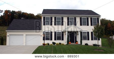 new colonial home with two car garage and cement driveway. poster