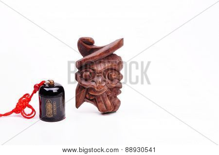 Small Feng Shui Bell and Demon Amulet on White Background