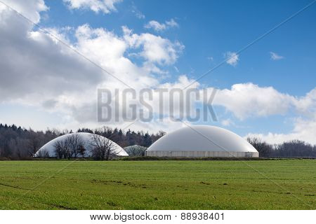Biogas Plant Behind A Wide Field Against Blue Sky