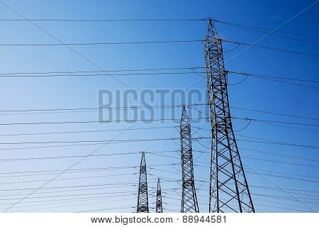 Row of numerous high-voltage heavy-duty industrial pylons for electricity distribution. Parallel wires on a blue sky background. Power energy and electricity infrastructure concept. poster