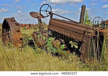Rusty old tractor missing front wheels