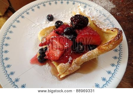 a crepe desert on a plate with strawberries blueberries and powder sugar