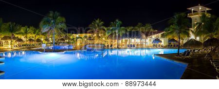 Panorama of hotel and swimming pool at night,