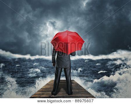 Man with umbrella standing on the pier